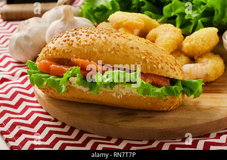 Open sandwich with cream cheese, salmon and salad on a cutting board - Stock Image