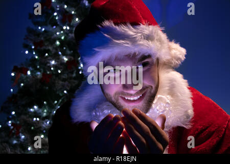 Good looking male santa smiling and holding lights in his hands in front of christmas tree - Stock Image