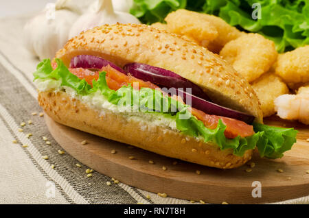 Sandwich with cereals bread, salmon, salad and onion on a cutting board - Stock Image