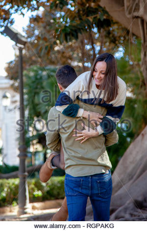 A boy takes his girlfriend in his arms in a public park - Stock Image