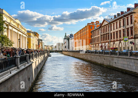 St. Petersburg, Russia - September 10 2018: Tourists crowd the square of the Spilled Blood Cathedral next to Griboyedov Channel off the Moyka River - Stock Image