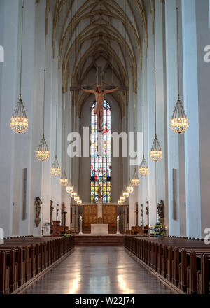 Munich, Bavaria, Germany - May 29, 2019. Interior of Frauenkirche facing the altar and no person, vertical composition, including Jesus hanging from t - Stock Image