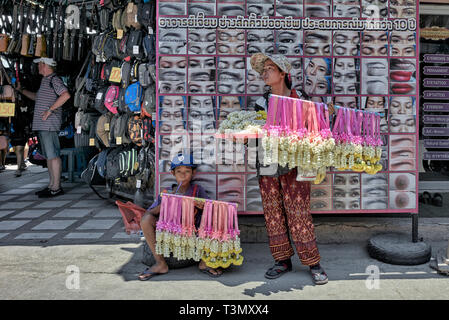 Thailand street vendor. Mother and her child selling scented flowers against an eye catching billboard - Stock Image