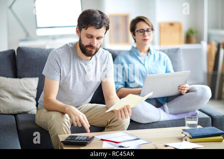 Young man with payment bill making calculations while his wife networking on sofa near by - Stock Image