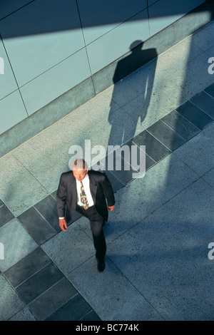 overhead view of businessman walking with shadow - Stock Image