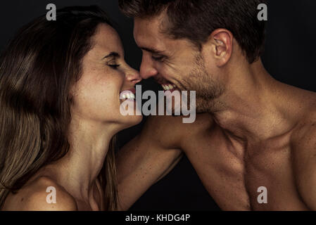 Happy couple nuzzling, side view - Stock Image