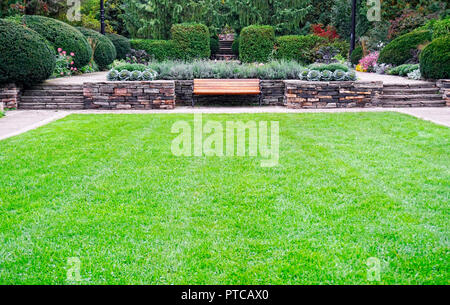 Formal garden design with stoneworks, flowerbeds, perennial flowers,lawn, hedges and trees in Alexander Muir Memorial Park in North Toronto, Ontario,  - Stock Image
