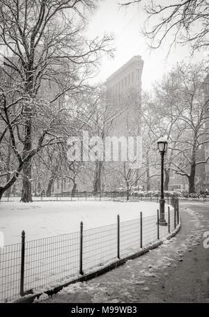 New York City, NY, USA - March 21, 2018: Flatiron Building from Madison Square Park with snowfall. (Black & White) Flatiron District, Manhattan - Stock Image