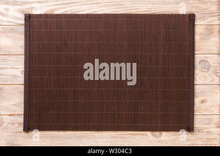 Empty Asian Food Background. Dank Bamboo mat on brown wooden background top view with copy space flat lay. - Stock Image