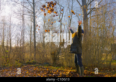 Woman throwing leaves in the air in autumn - Stock Image