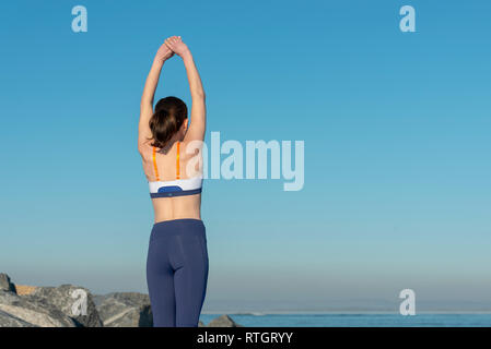 back view of a woman doing an arm stretch outdoors, morning warm up exercises - Stock Image
