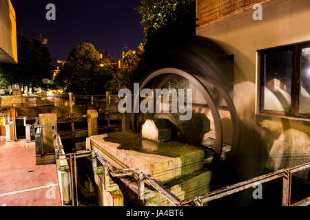 Fabulous water mill in the center of the city at night. Old architecture. - Stock Image