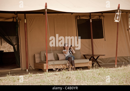 Tanzania, Serengeti. A guest looks out over the plains from the comfort of her tent at Lemala Ewanjan. MR. - Stock Image
