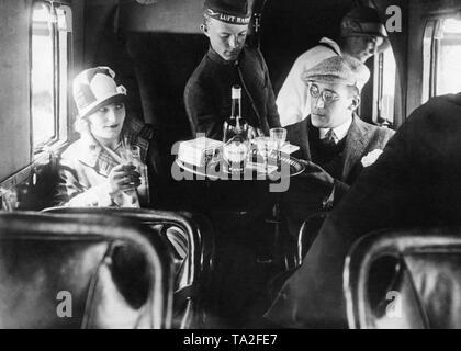 A Lufthansa steward serves passengers aboard an aircraft. - Stock Image