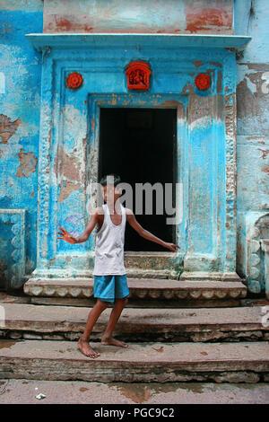 Kid stands in front of a door in Caranasi, India - Stock Image