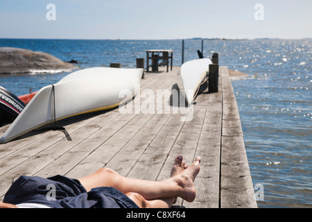 Woman sunbathing on a jetty in the Archipelago of Stockholm, Sweden. - Stock Image
