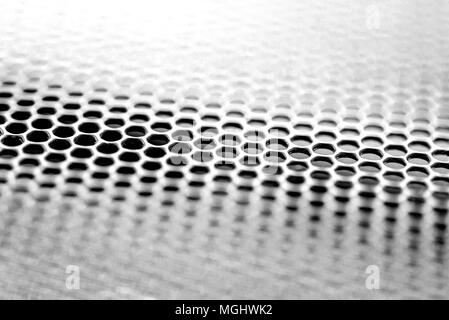 Black and white mesh grill detail with defocused area creating an abstract metal style background - Stock Image