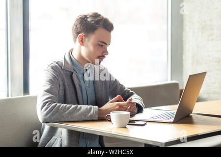 Portrait of young successful serious businessman working on computer sitting in office. thoughtful entrepreneur connecting to wireless via computer, i - Stock Image