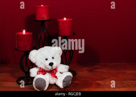 Three red candles in metal holders and red rose, one teddy bear on wooden table. - Stock Image