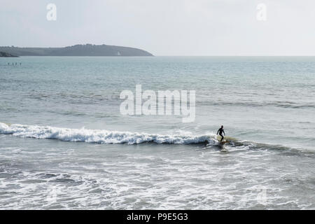 Surfer wearing wet suit riding ocean wave close to shore. - Stock Image