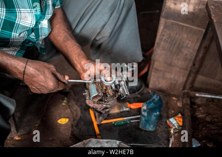 A mechanic in a small workshop in India, repairing the carburettor on an old motorcycle. - Stock Image