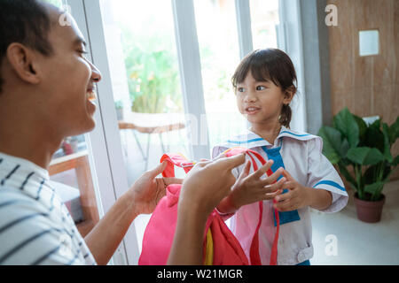 kindergarten student wearing school uniform and put backpack on ready for school - Stock Image