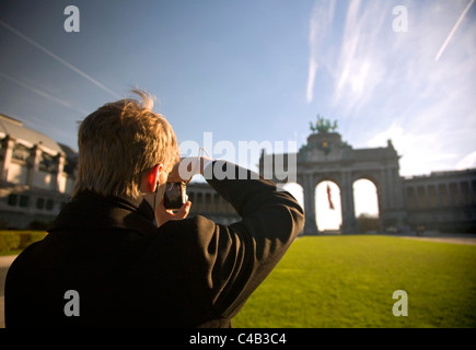 Brussels, Belgium; A young man taking a photo of the Triumphal Arch at the 'Parc du Cinquantenaire' on his - Stock Image