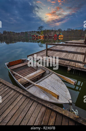 Tata, Hungary - Fishing boat by Lake Derito (Derito to) with wooden fishing cottages and beautiful sunset - Stock Image