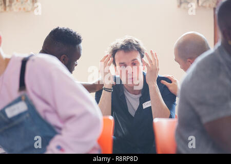 Men comforting man talking in group therapy - Stock Image