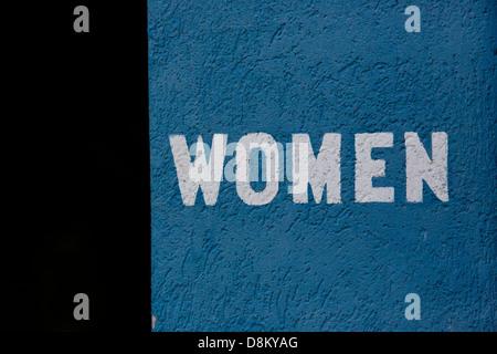 Word 'WOMEN' written on a bright blue wall - Stock Image