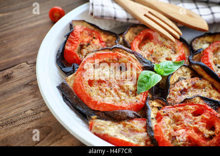 Tasty pizza topping, roasted aubergine with tomatoes and basil on the plate on the wooden table, delicious homemade - Stock Image