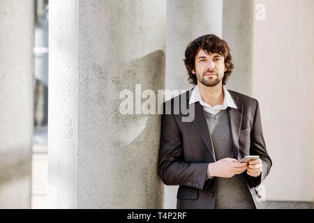 Young man leans on column with smartphone in hand, North Rhine-Westphalia, Germany - Stock Image