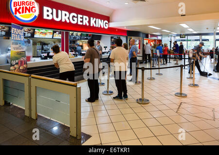 People queuing at Burger King in a motorway service station. Several large customers in the foreground. - Stock Image