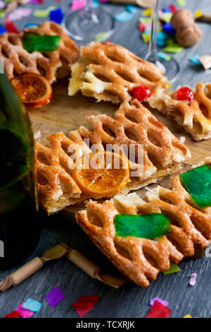 some slices of coca de Sant Joan, a typical sweet flat cake from Catalonia, Spain, eaten on Saint Johns Eve, on a rustic table, next to a bottle of ch - Stock Image