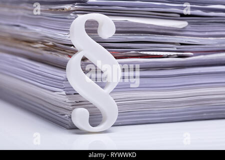 Close-up Of Red Paragraph Symbol Leaning On Documents - Stock Image