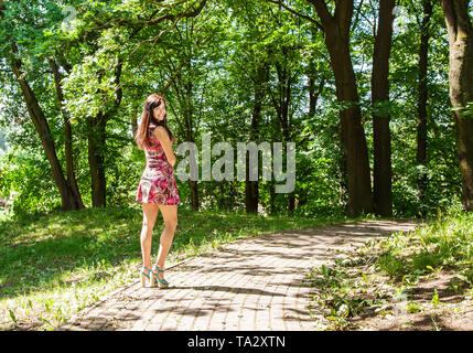 young beautiful woman in red dress standing on the alley in the park on bright sunny summer day - Stock Image