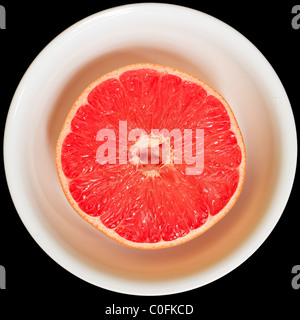 Ruby-red grapefruit in a white bowl on a black background - Stock Image