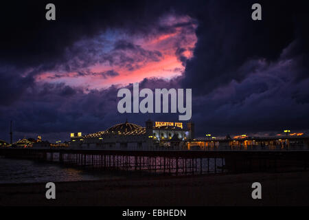 Storm clouds and sunset over Brighton Pier - Stock Image
