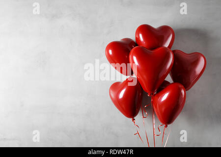 Heart shaped foil balloons on concrete wall background - Stock Image