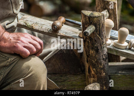Craftsman making wooden knobs on a shave horse - Stock Image
