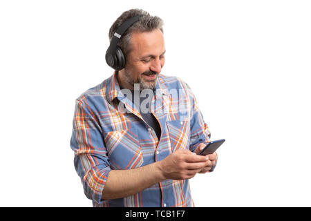 Smiling man texting on phone and listening to music with headphones isolated on white background - Stock Image