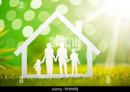 Close-up Of Paper Cut Out Of Family House On Grassy Field - Stock Image