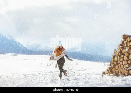 Happy young girl runs at first snow in mountains - Stock Image