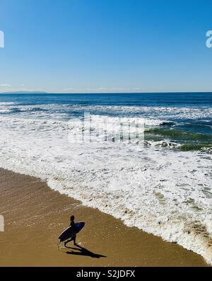 Female surf walking out to surf. Manhattan Beach, California USA. - Stock Image