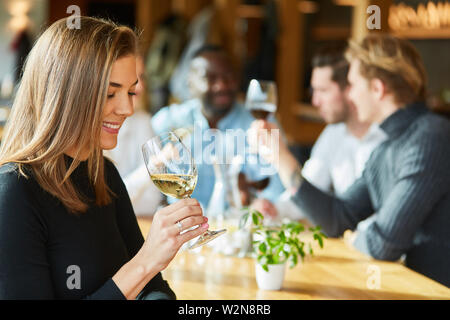 Young woman with friends in the restaurant is drinking a glass of white wine - Stock Image