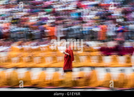 Buddhist monk carrying offerings during ceremony at Paro religious festival Bhutan - Stock Image