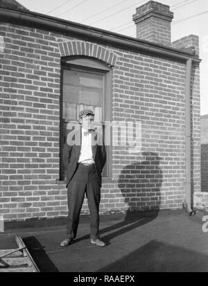 A dapper man poses with his shadow on a rooftop, ca. 1925. - Stock Image