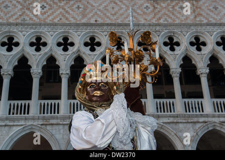 Venice, Italy. 25th Feb, 2014. A masked man carries a light stand outside of the Doge's Palace in an African inspired costume. Venice Carnivale Credit:  MeonStock/Alamy Live News - Stock Image