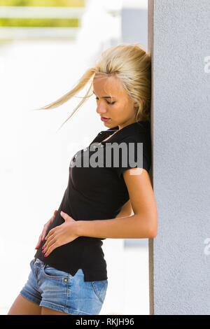Painful womanly illness teen girl touching stomach - Stock Image