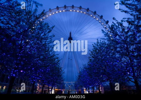 British Airways London Eye at Twilight with trees in the foreground lit with blue lights - Stock Image